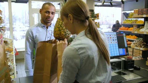 Positive satisfied mixed race male customer buying fresh organic products at local grocery store. Female cashier packing pineapple and products into grocery bag for client after billing in small shop.