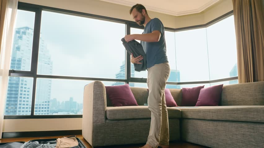 Handsome man packs a suitcase in a room with a panoramic window overlooking the skyscrapers | Shutterstock HD Video #1023051352
