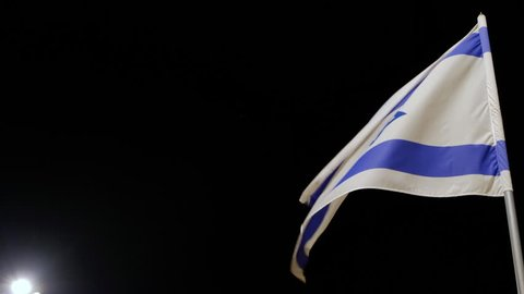 4K. Flag of the State of Israel develops on a flagstaff on wind at night against the background of the black sky and in the left bottom corner of a shot the lamp is visible.