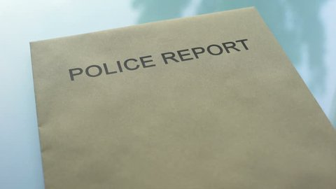 Police report top secret, hand stamping seal on folder with important documents