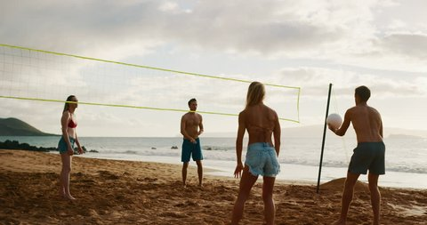 Active friends playing beach volleyball, slow motion serve set rally