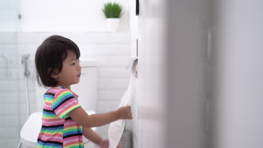 Toddler pulling out toilet paper while playing around in the bathroom | Shutterstock HD Video #1023156112