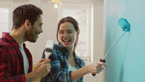 Beautiful Couple Decorate Their New Apartment and Fool Around. Husband and Wife are Painting the Wall with Rollers that are Dipped in Light Blue Paint. They are Happy and Have Fun. Renovations at Home