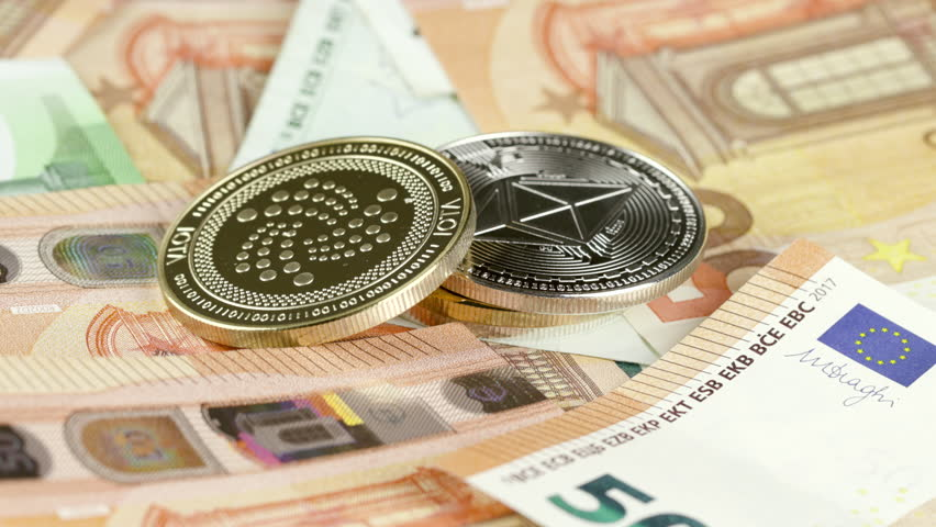 IOTA token lying on top of euro bills. The golden coin on the bills can symbolize the monetary value growth/decline by investment or the value that is inherent in the technology.