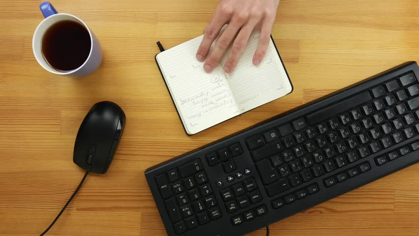 A man in the office writes tasks for the day in the diary on a wooden table. Top view | Shutterstock HD Video #1023226042