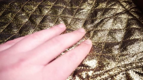 Male hand slides over smooth synthetic golden nylon and polyester fabric. 4k footage.