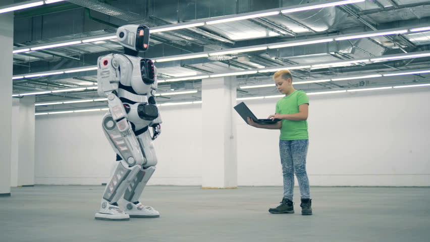 Teenage boy is manipulating a robot with his laptop | Shutterstock HD Video #1023238942