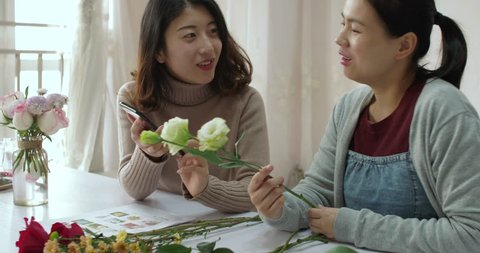 chinese beautiful young florist is teaching her female friend flower arrangement skills. she using cellphone to show her the information about Platycodon grandiflorum