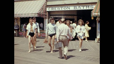 1930s: Men in bathing suits leave change room. People in summer wear walk to beach. Lifeguard chair w/ Temp 76 degrees. Regulations prohibit refuse, ball playing, dogs, picnic baskets, and disrobing.