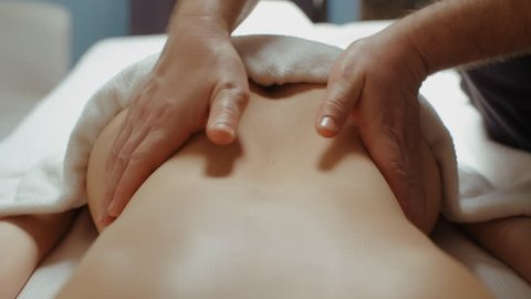 Male masseur doing back lumbar massage. Slim woman receiving health procedure in spa salon, relaxing lying on massage table