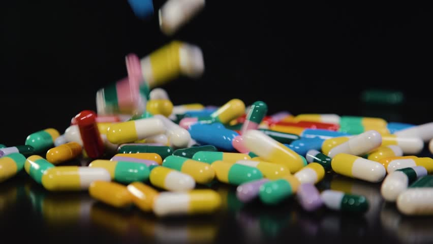 Pharmaceutical drug, a bunch of multi-colored round capsules of tablets with antibiotic medicine in packages. Disease treatment concept, video in motion