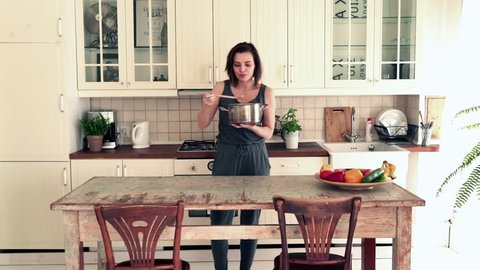 Young, beautiful woman trying tasteless soup and spit it out