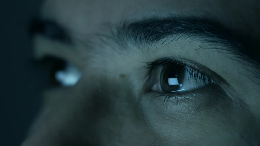 Screen reflected on man's eyes looking up. Man looking at a screen in the dark.  | Shutterstock HD Video #1023325882