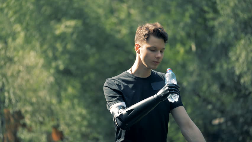 Prosthetic hand holding a bottle. Human with a robot arm. | Shutterstock HD Video #1023388012