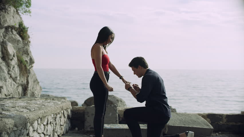 Loving Italian boyfriend proposes to his girlfriend who happily accepts and they hug each other, with view of the ocean and coast line in the background, on bright sunny day.