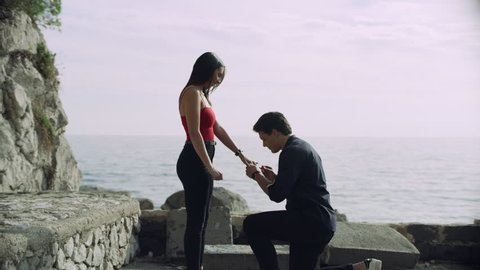 Loving Italian boyfriend proposes to his girlfriend who happily accepts and they hug each other, with view of the ocean in the background, on bright sunny day. Wide shot on 8k helium RED camera
