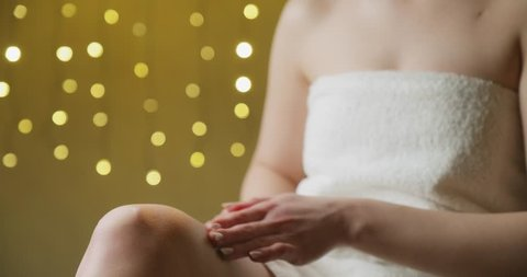 Young woman applying moisturizer cream on the knee. Concept of depilation, smooth skin, skincare and body