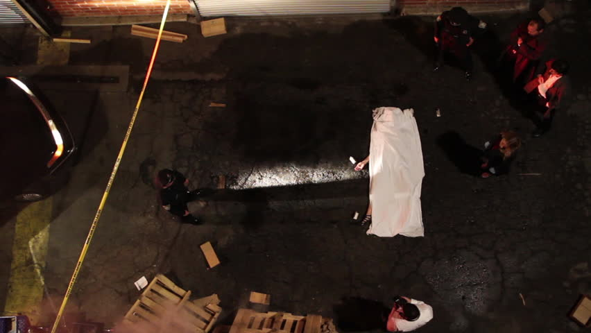 Overhead shot of an alley at night with an active homicide crime scene being investigated by law enforcement. Police and detectives walk around the victim's body while a crime scene photographer takes