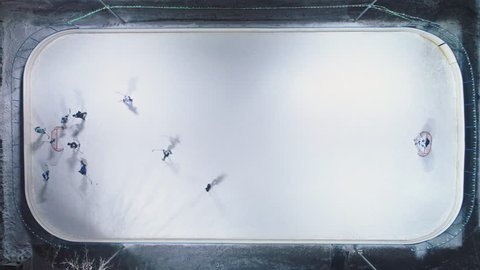 Players on Ice Rink Playing Hockey. Aerial Vertical Top-Down View. Static Drone Shot