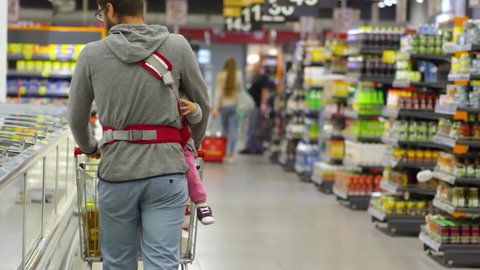 Rear view of man pushing shopping cart and carrying little baby in sling while buying food at supermarket