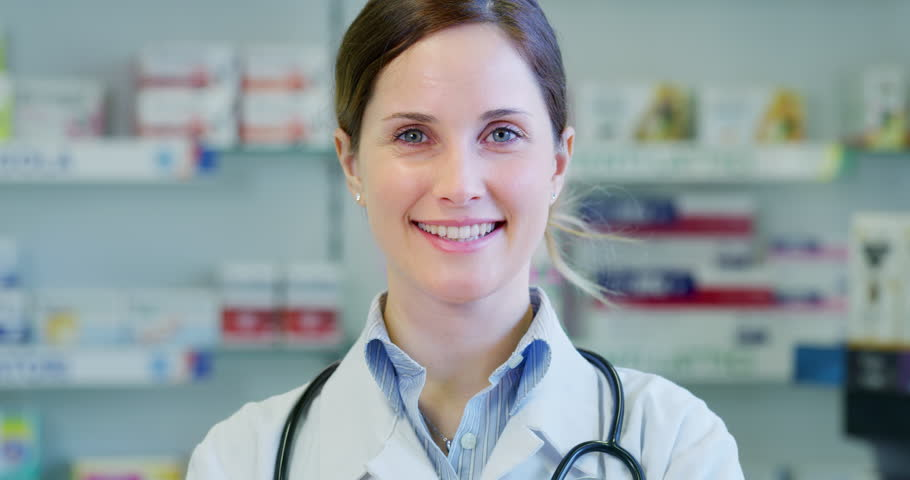 Slow motion close up of a beautiful young woman pharmacist consultant smiling in camera. Shot in 8K. Concept of profession, medicine and healthcare, medical education, pharmaceutical sector