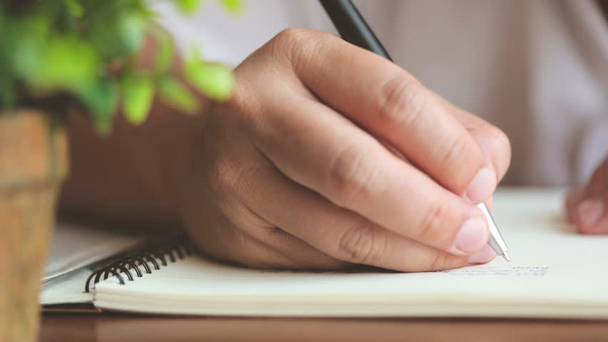 Close up hands writing on the diary book in living room  | Shutterstock HD Video #1023640972