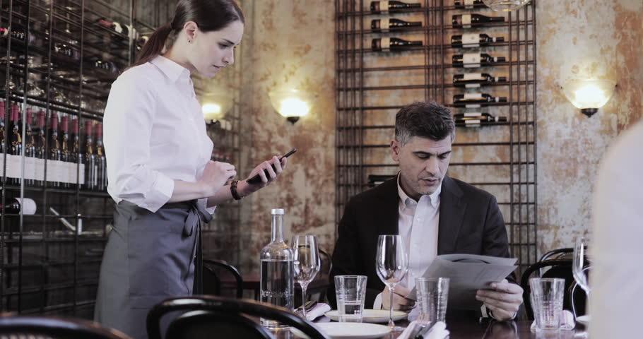 Waitress taking food order on digital device in restaurant   Shutterstock HD Video #1023646162