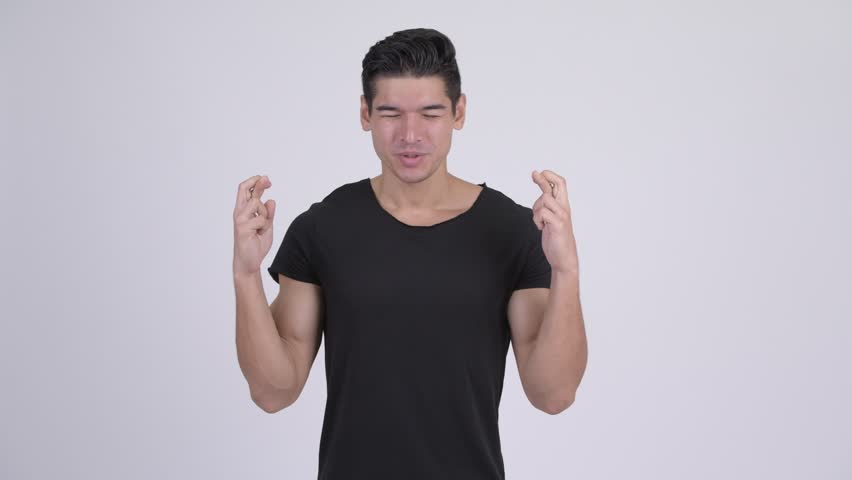 Young handsome multi-ethnic man wishing with fingers crossed | Shutterstock HD Video #1023660592