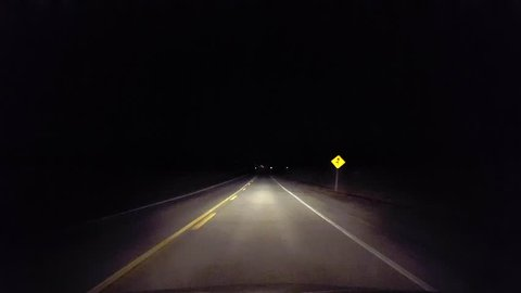 Driving Rural Countryside Road Into the City at Night.  Driver Point of View POV Entering Urban Lights From Country Street
