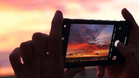 Female Hands Holding Smartphone and Doing Nature Photography. Young Tourist Woman Taking Photos with Mobile Phone Camera of Amazing Sunset at the Beach. 4K Slowmotion. Bali, Indonesia.