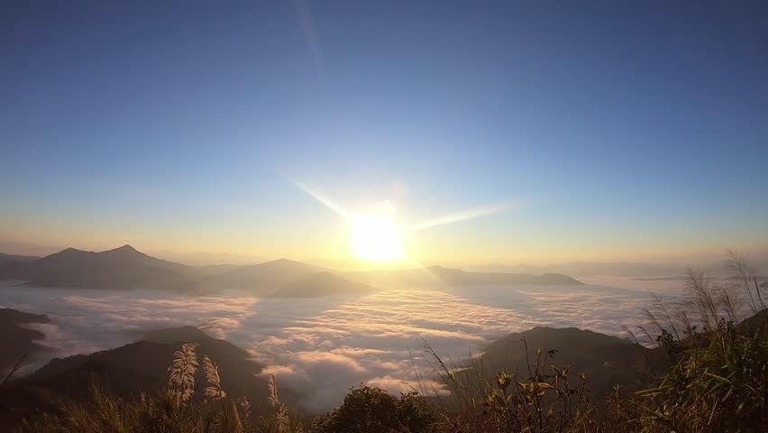 Time lapse of sunrise and sea of fog moves past the tops of the mountains in Doi Pha Tang, Chiang rai, Thailand. #1023699982