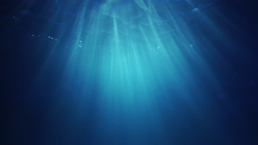 Underwater sunlight beams shining from above coming through the deep crystal clear blue water causing a beautiful water lighting reflections curtain #1023726232