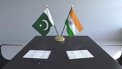 Flags of Pakistan and India and papers on the table. Negotiations and signing an international agreement. Conceptual 3D animation