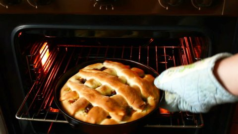Barmy apple jam pie in an oven.