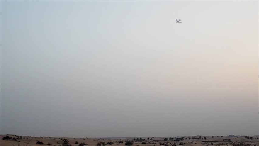 Plane flies in the sky over the desert. Silhouette of the aircraft | Shutterstock HD Video #1023752032