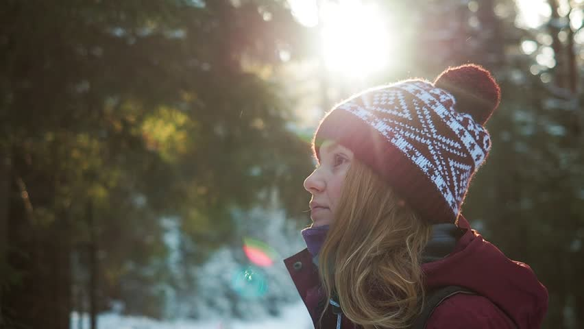 Beautiful woman standing among snowy trees in winter forest and enjoying first snow falling. Wearing hat, hipster style. Wanderlust and exploring nature. Fairytale forest winter vacation. | Shutterstock HD Video #1023763672