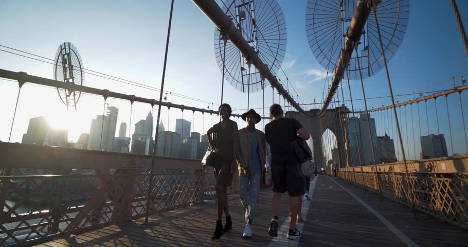 New York, New York / United States - September 18 2018: Young Black Couple Walk Brooklyn Bridge, Lens Flare Sunset NYC Skyline | Shutterstock HD Video #1023767902