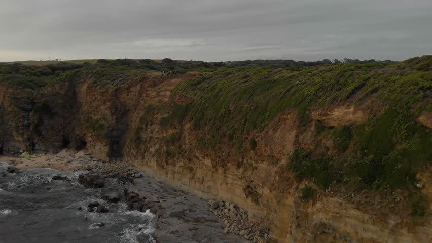 Aerial shot of cliffs on Bass coast with cars parked on top. | Shutterstock HD Video #1023804202