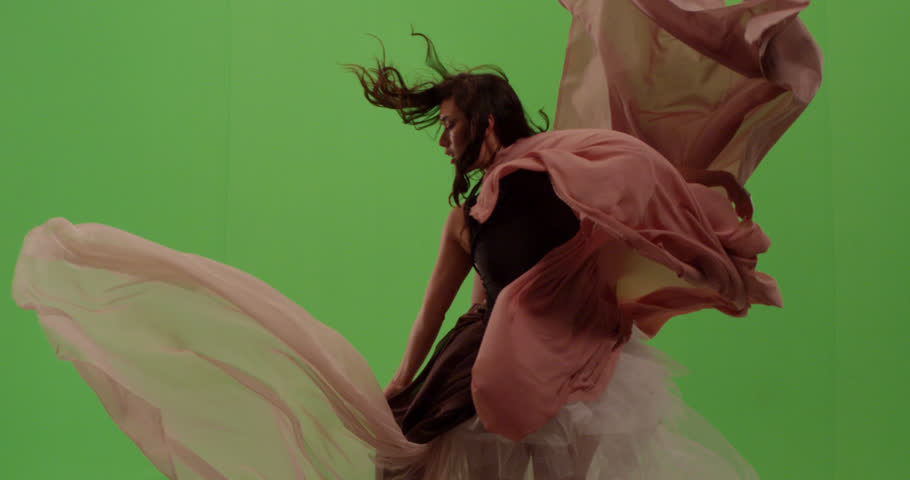 Beautiful fashion model dancer posing against green screen surrounded by flowing fabric