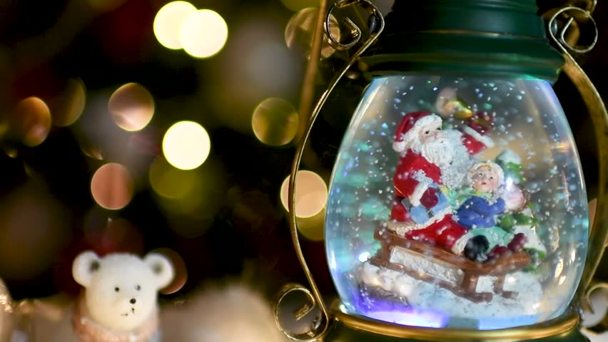 Beautiful snow globe with Santa Claus and child on sleigh with Christmas lights blurred in the background. Flat plane