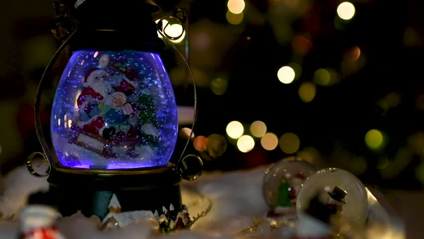 Beautiful Christmas decoration with snow globes on the table and lights blurred in the background. Flat plane