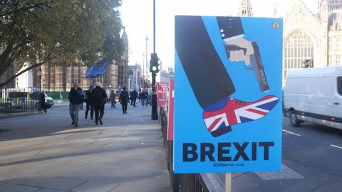 London, UK - Feb 7, 2019: Anti-Brexit placard outside, Westminster, London, UK depicting Brexit as shooting the UK in the foot. Anti-Brexit protestors visible in background