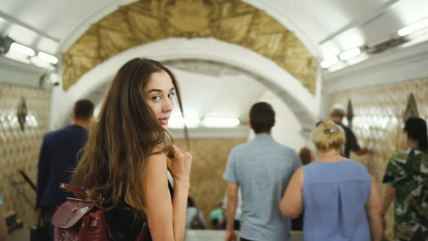 A beautiful girl is walking along the underpass in the subway close up among a large number of people. The woman turns and looks at the camera. Cute human in subway station. Beauty people. | Shutterstock HD Video #1023917902