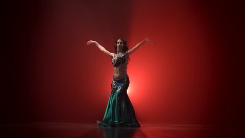 Torso of woman belly dancer dancing . Red smoke background