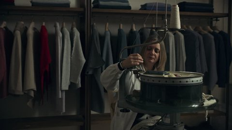 In a sewing workshop, an Italian seamstress uses a sewing machine to make clothing. Close up on 8k helium RED camera.