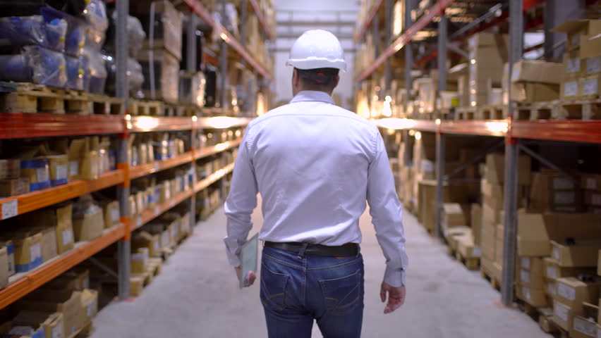 Follow footage of employees male warehouse worker engineer in hard hat working. walking through logistics center warehouse factory construction site logistics architect businessman man builder indoors | Shutterstock HD Video #1023937292