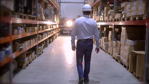 Follow footage of employees male warehouse worker engineer in hard hat working. walking through logistics center warehouse factory construction site logistics architect businessman man builder indoors