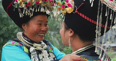 Human emotion: Miao woman in laojiazhai village hugging, dressed it traditional cultural costume. Minority people in china villages. Slow motion, red cinema camera, hand held.