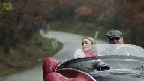 Older boyfriend driving in a convertible sports car with his younger girlfriend, as she throws her scarf in the air happily. Medium shot on 8k helium RED camera.