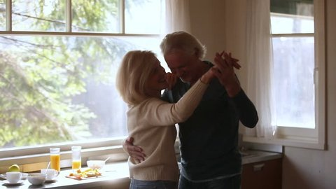 Happy mature senior couple dancing laughing in the kitchen, beautiful romantic middle aged older grandparents relaxing having fun together at home celebrating anniversary enjoy care love tenderness
